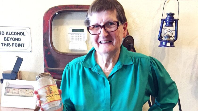 Dorothy Maurath holds the Ramona Maid Pickle Company jar after stopping in at Reds, Whites & Brews to see it.