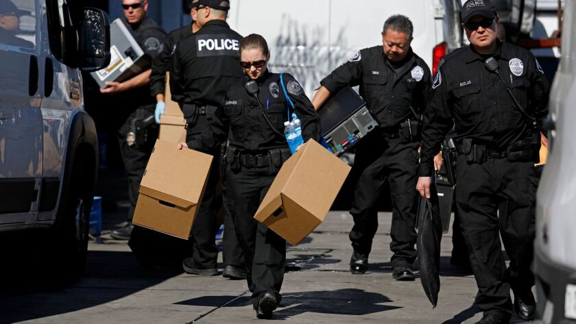 Investigators with the Los Angeles County district attorney's office remove computers and boxes from Mayor Ramon Medina's Maywood auto shop on Feb. 8.