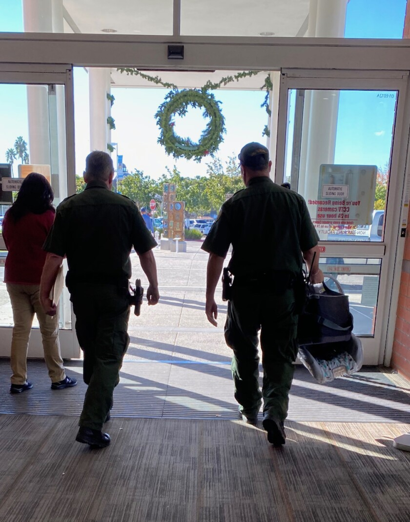 Border Patrol agents leave Scripps Mercy hospital in Chula Vista with a baby car seat.