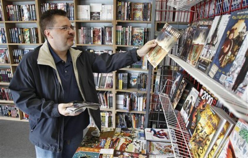 Ron Bufalini, from Ambridge, Pa., looks over the free comic books available at the New Dimensions Comics store on Free Comic Book Day, Saturday, May 7, 2011 in Cranberry, Pa. Bufalini says he likes to take advantage of the annual give away to look into different genres of comic books as well as get