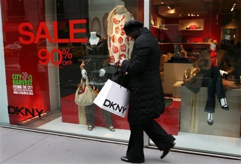 In this Jan. 5, 2009 file photo, a woman leaves a DKNY clothing store on New York's Madison Ave. Pricing goods within reach of strapped consumers is a big focus for many retailers, given the way nervous consumers have stopped shopping.  (AP Photo/Mark Lennihan, file)