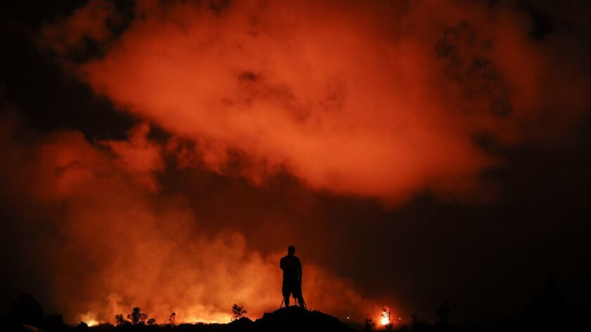 A man photographs lava erupting from Kilauea.