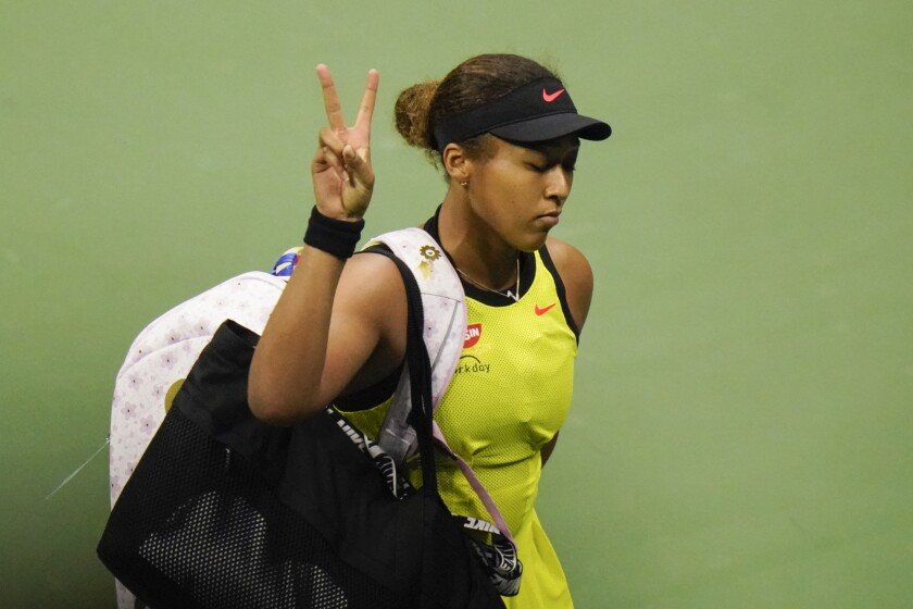 Naomi Osaka flashes a peace gesture to fans after losing to Leylah Fernandez at the U.S. Open on Friday.