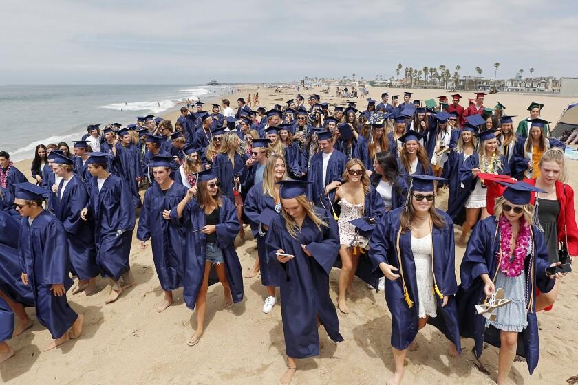 Newport-Mesa Unified School District seniors walk along the coast on Friday.