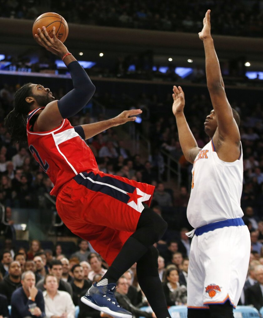 Washington Wizards center Nene Hilario (42) shoots over New York Knicks center Kevin Seraphin (1) in the first half of an NBA basketball game at Madison Square Garden in New York, Tuesday, Feb. 9, 2016. (AP Photo/Kathy Willens)