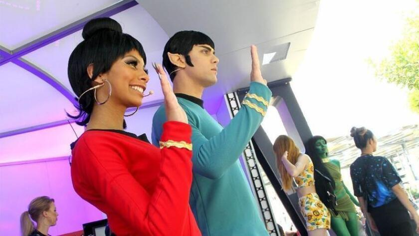 Ariana Nova, left, and Dakota Shapiro, dressed as Star Trek characters wave to the crowd at Comic-Con 2016. (John Gastaldo/Union-Tribune)
