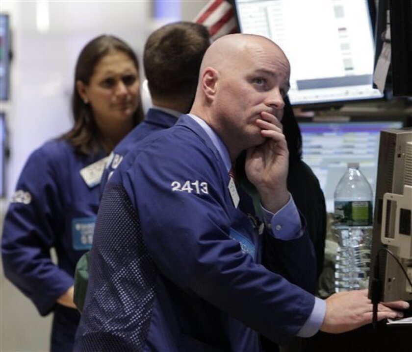 FILE - In this Dec. 12, 2011 file photo, specialist John O'Hara, right, works on the floor of the New York Stock Exchange. Stock markets retreated slightly Wednesday, Jan. 4, 2012, after a surprisingly buoyant start to the new year triggered by a run of encouraging U.S. economic data. (AP Photo/Richard Drew, File)