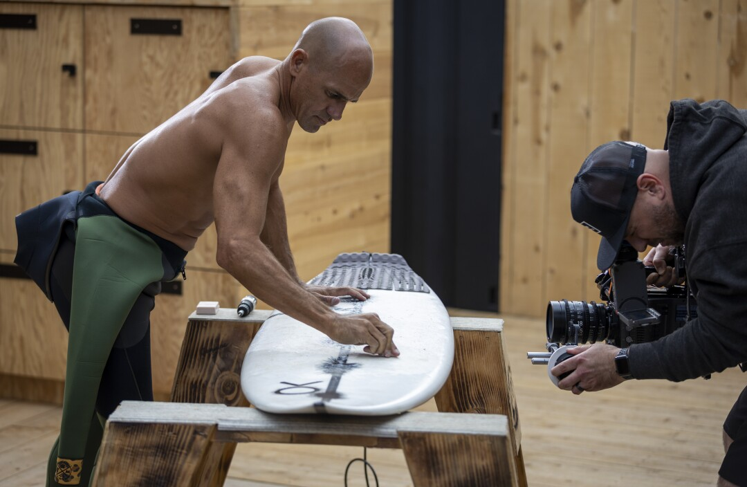"""Kelly Slater waxes his board on the set of """"The Ultimate Surfer."""""""