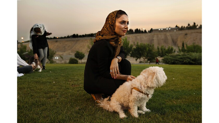 Susan Mokhtiari, 39, in a Tehran park with her terrier Rubeena.