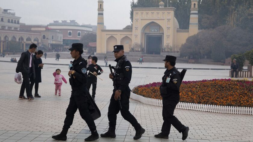 FILE - In this Nov. 4, 2017 file photo, Uighur security personnel patrol near the Id Kah Mosque in K