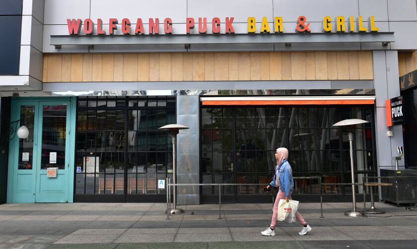 A pedestrian walks past a closed Wolfgang Puck Bar & Grill restaurant in Los Angeles. To slow the coronavirus epidemic, dine-in services has been halted at the city's restaurants.