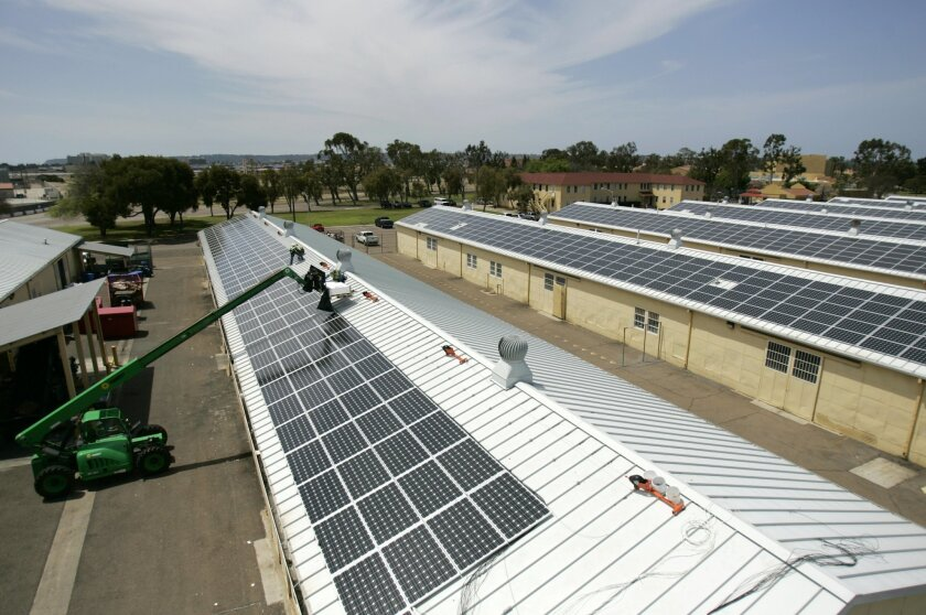 Workers from Independent Energy Solutions install solar panels on several buildings at the Marine Corps Recruit Depot on Wednesday.