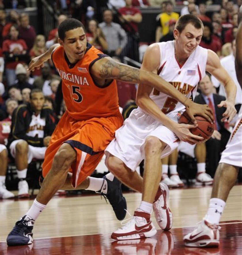 Virginia's Sylven Landesberg, left, and Maryland's Eric Hayes, right, get a hand on the ball during the first half of an NCAA college basketball game Tuesday, Jan. 20, 2009, in College Park, Md. (AP Photo/Nick Wass)