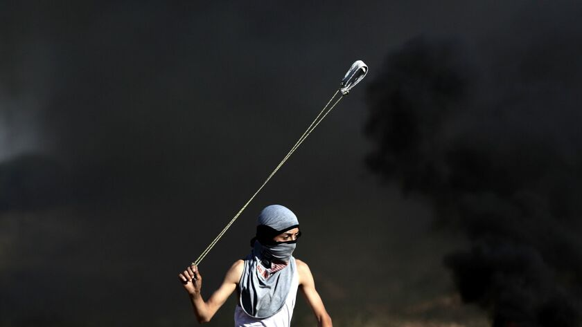 epa05993367 A Palestinian protester throws a stone during clashes with Israeli troops after a protes