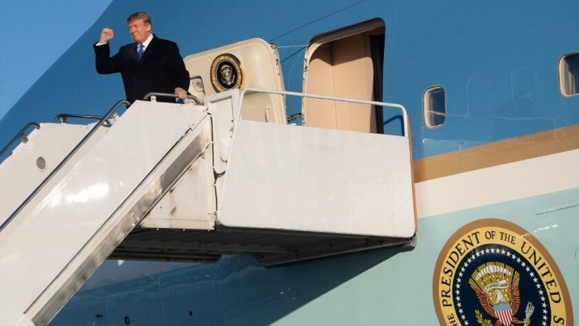 President Trump disembarks Air Force One during a refueling in Alaska on his way back to Washington from a summit with North Korea's Kim Jong Un.