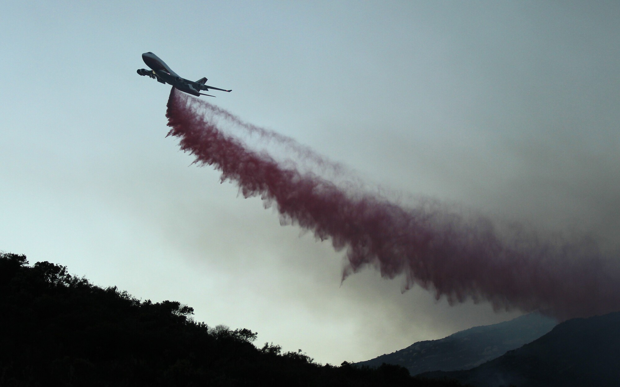 A 747 tanker drops fire retardant along Lyons Valley Road during the Valley Fire on Sunday, Sept. 6, 2020.