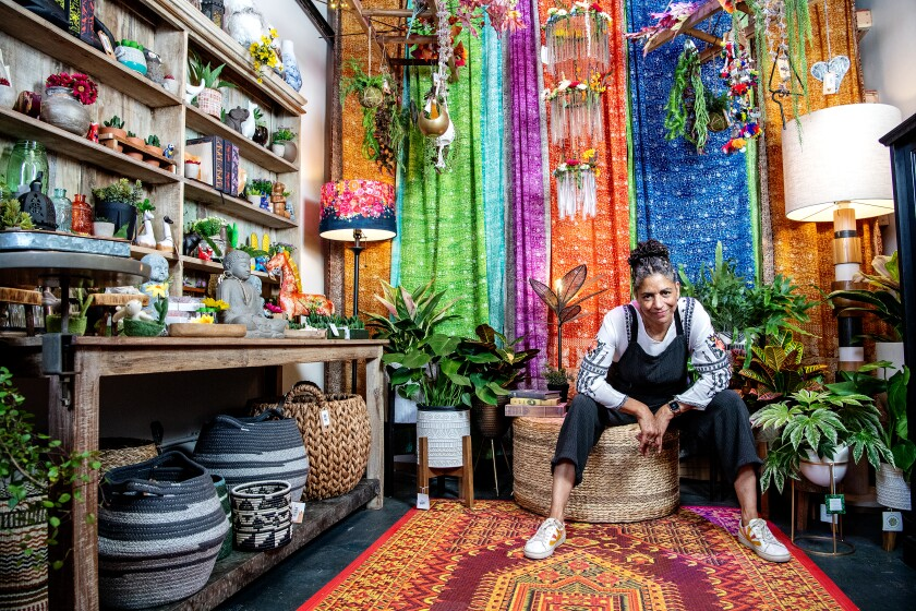 A seated woman surrounded by colorful plants and fabrics.