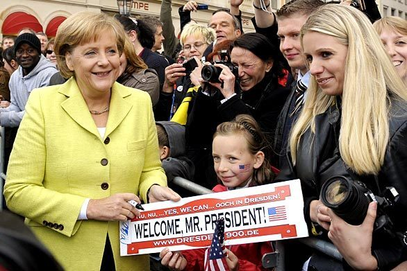 German Chancellor Angela Merkel autographs a sign held by a young girl welcoming President Obama to the eastern German city of Dresden, which was rebuilt after being repeatedly bombed by the Allies in World War II.