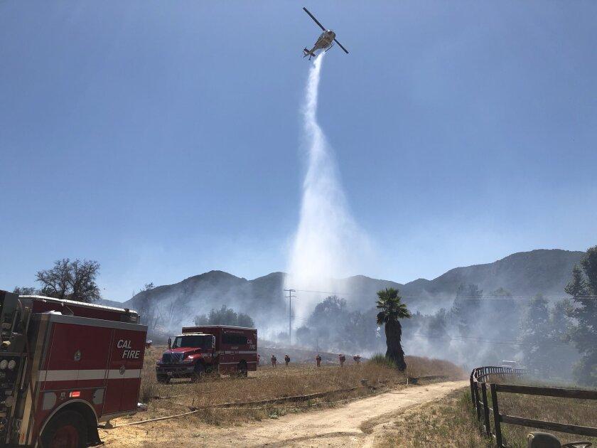 Cal Fire battles a brush fire in De Luz on Saturday.
