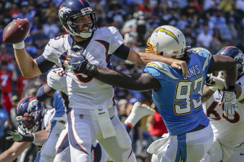 Broncos quarterback Joe Flacco tries to get off a pass while getting hit by Chargers defensive tackle Justin Jones on Sunday.