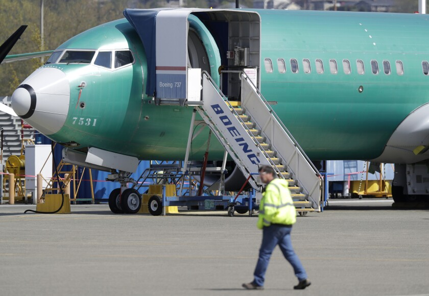 FILE - In this April 26, 2019, file photo a worker walks past a Boeing 737 MAX 8 airplane being built for Oman Air at Boeing's assembly facility in Renton, Wash. Orders and deliveries of new Boeing planes remain depressed eight months into the grounding of the company's 737 Max, Boeing said Tuesday, Nov. 12. (AP Photo/Ted S. Warren, File)