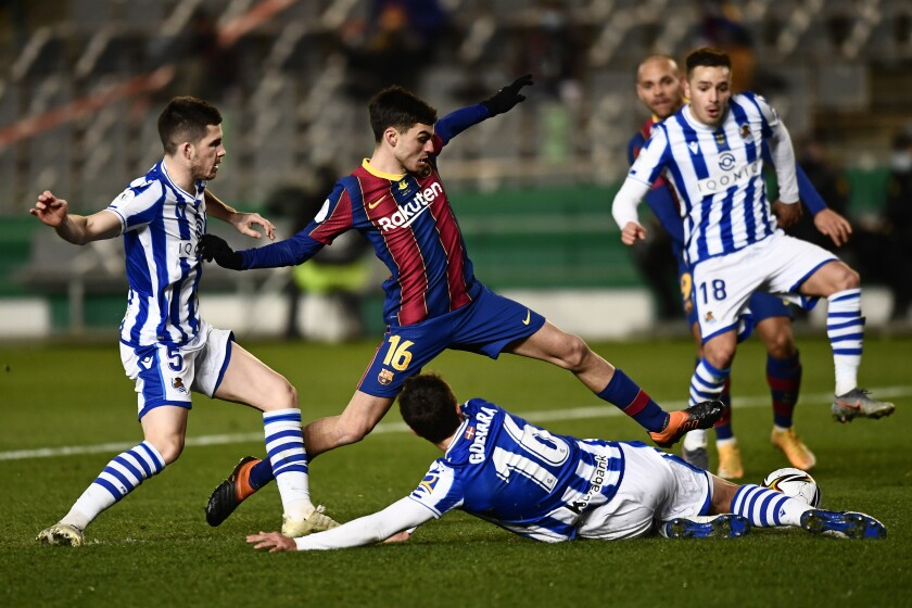 Barcelona's Pedri, center, battles for the ball with Real Sociedad defenders during Spanish Super Cup semi final soccer match between Barcelona and Real Sociedad at Nuevo Arcangel stadium in Cordoba, Spain, Wednesday, Jan. 13, 2021. Barcelona will play the final after defeating Real Sociedad 3-2 in a penalty shootout after the game ended 1-1. (AP Photo/Jose Breton)