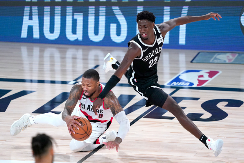 Portland's Damian Lillard chases the ball in front of Brooklyn's Caris LeVert on Thursday in Lake Buena Vista, Fla.