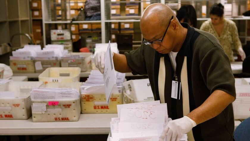 Absentee ballots are sorted in San Francisco in 2008. State law requires voters be allowed to mail in ballots, but the mandate was suspended when the state cut funding.