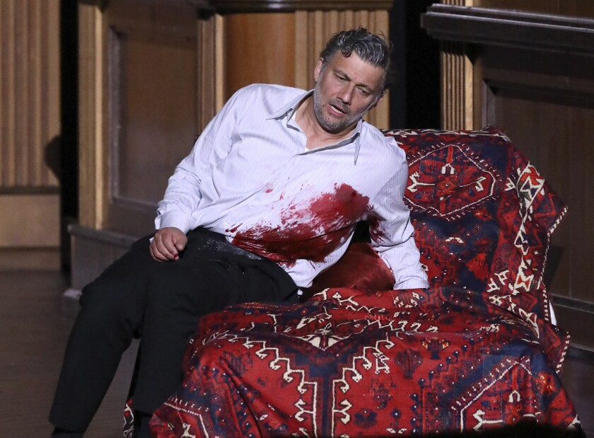"""This image released by the Bavarian State Opera shows tenor Jonas Kaufmann as the mortally wounded Tristan during a rehearsal for his role debut in a new production of Wagner's """"Tristan und Isolde,"""" premiering at Munich's Bavarian State Opera on June 29. (Wilfried Hösl/Bavarian State Opera via AP)"""