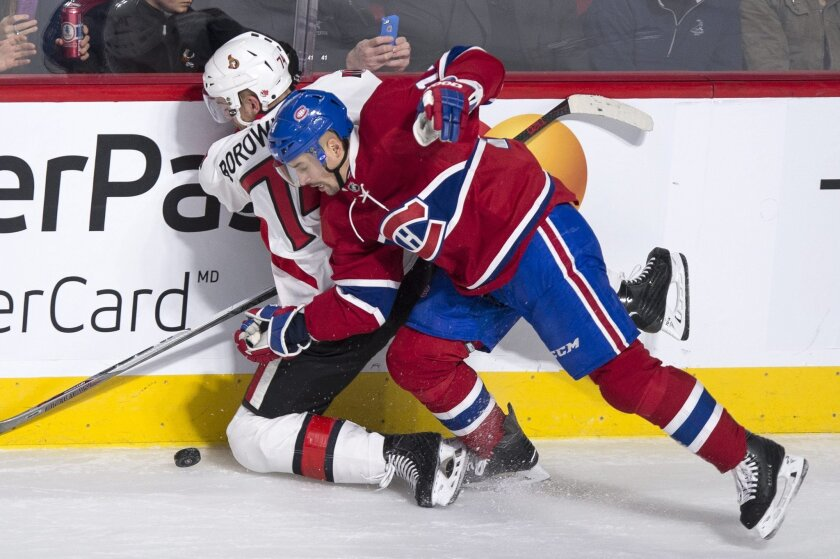 Ottawa Senators' Mark Borowiecki, left, is sent into the boards by Montreal Canadiens' Tomas Plekanec during the second period of an NHL hockey game Tuesday, Nov. 3, 2015, in Montreal. (Paul Chiasson/The Canadian Press via AP)