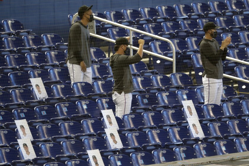 Miami Marlins players, sitting among photographs of their teammates, cheer as the team is introduced before a baseball game against the Atlanta Braves, Saturday, Aug. 15, 2020, in Miami. (AP Photo/Lynne Sladky)
