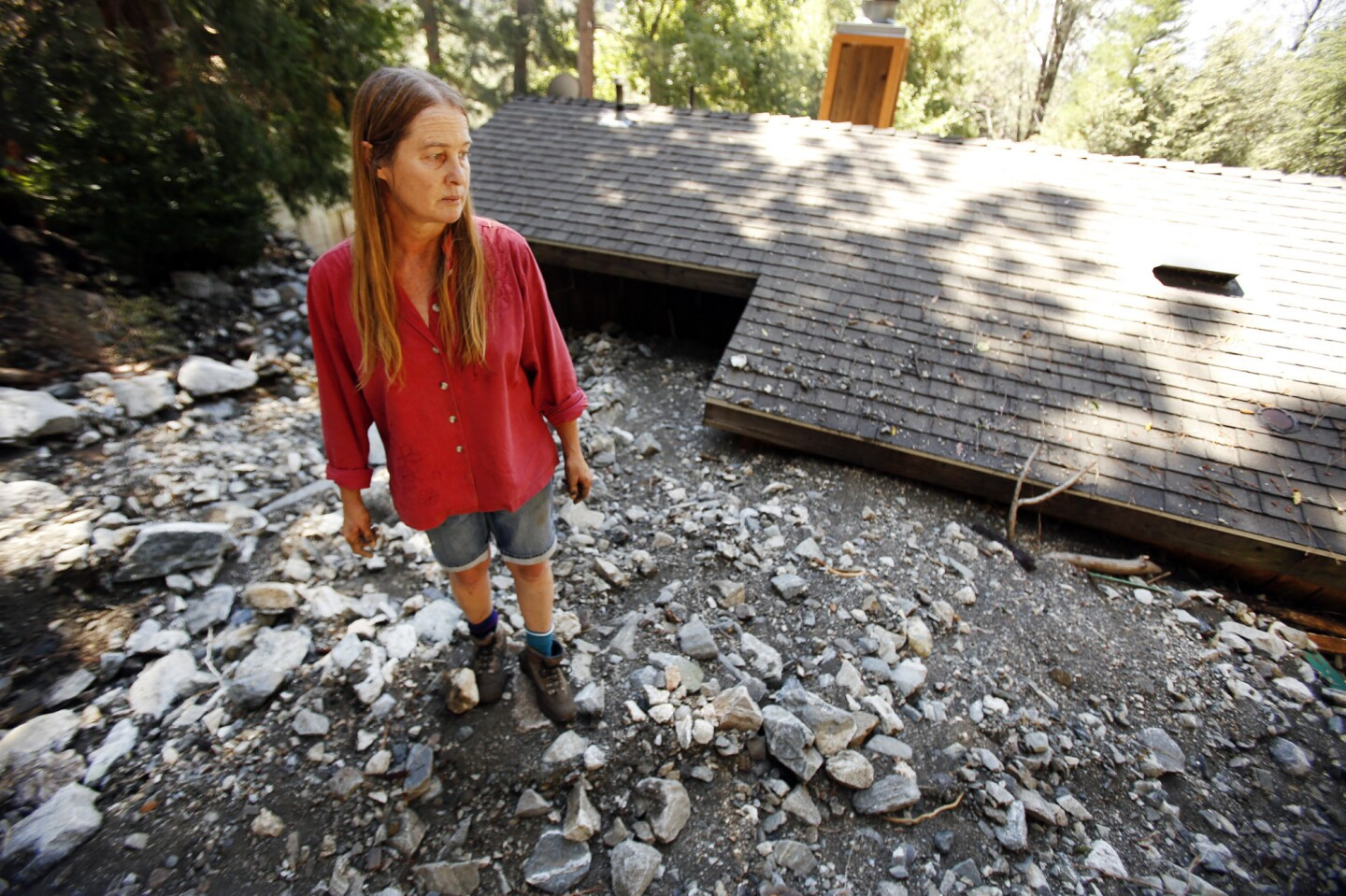 Michelle Olson walks around her house that was inundated with rocks and debris during Sunday's downpour.