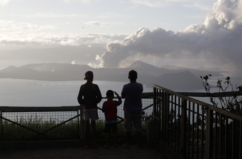 People watch the Taal volcano  Jan. 14 from Tagaytay, Philippines. The volcano is in the middle of a lake in Batangas province south of Manila.