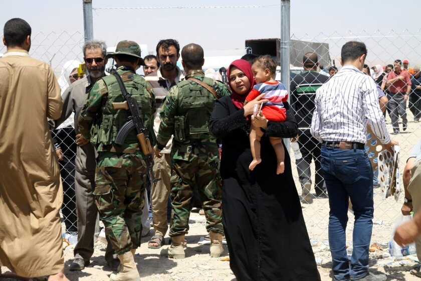 Soldiers search Iraqis who fled the violence in Mosul upon their arrival at a checkpoint in Irbil, Iraq, on June 11.