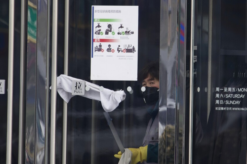 A cleaner wipes the glass door near instructions on hygiene at a clothing apparel store in Beijing, China Tuesday, Feb. 11, 2020. China's daily death toll from a new virus topped 100 for the first time and pushed the total past 1,000 dead, authorities said Tuesday after leader Xi Jinping visited a health center to rally public morale amid little sign the contagion is abating. (AP Photo/Ng Han Guan)