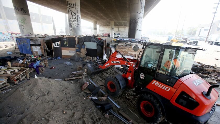 A worker clears a homeless encampment underneath the Santa Fe Avenue Bridge in Vernon in December.