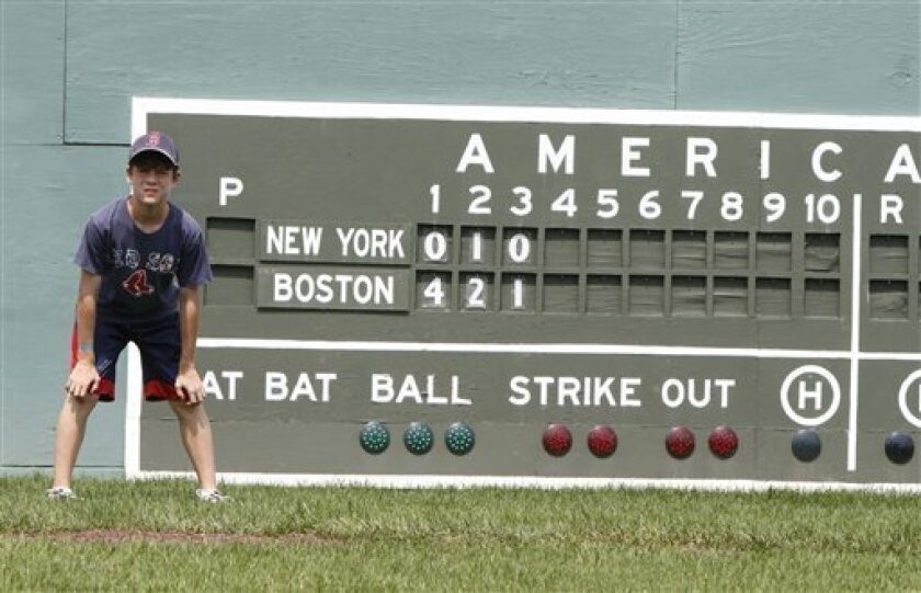 Nathan Colgrove stands in left field in front of the scoreboard at Little Fenway, a scaled-down version of the major league field in Essex, Vt., Monday, Aug. 2, 2010. Little Fenway is a unique 1/4th scale replica of Boston's Fenway Park in the backyard of Pat & Beth O'Connor's house in Essex, Vermo
