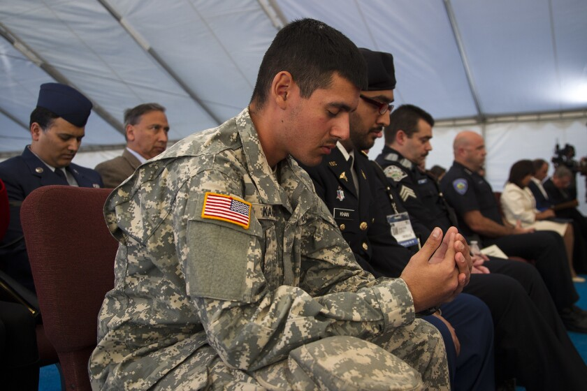 Army Pvt. Adeel Karim prays during a moment of silence for the San Bernardino shooting victims at the Jalsa Salana Convention at the Bait ul Hameed Mosque in Chino. Muslims from across the U.S. will confront the fears that non-Muslims have of Islam and delineate between true Islam and extremism.