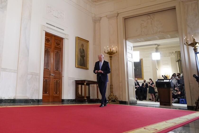 President Biden walks away from a lectern down an ornate hall