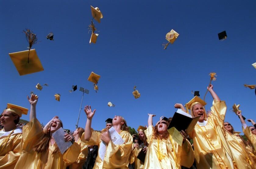 Ventura High Graduates toss their mortar boards into the air during graduation ceremonies.