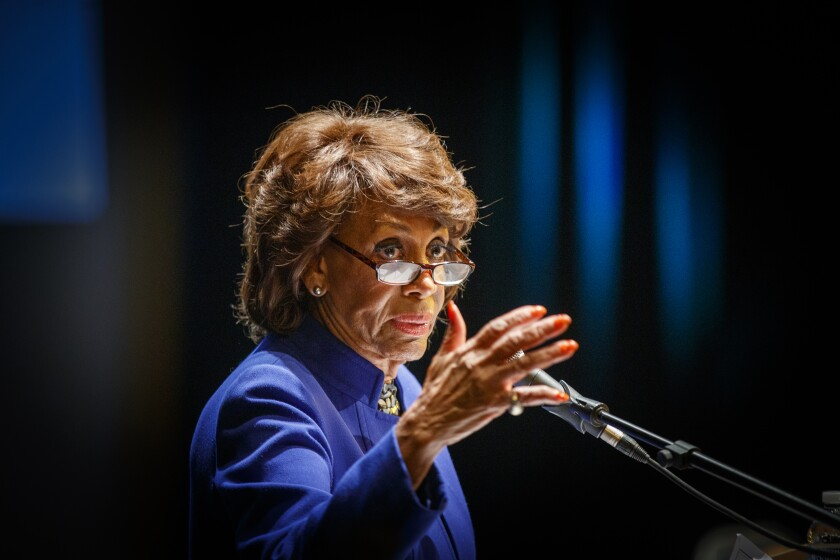 Rep. Maxine Waters gestures before a microphone