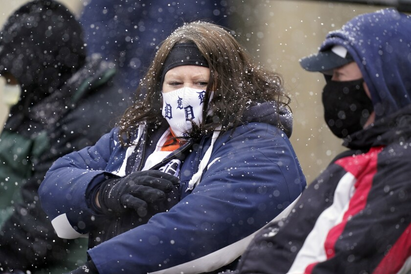Patty and Steve Smith watch the baseball game between the Detroit Tigers and the Cleveland Indians as snow falls, Thursday, April 1, 2021, in Detroit. (AP Photo/Carlos Osorio)