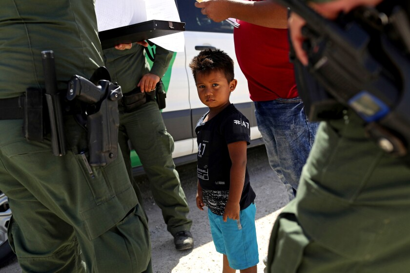 U.S. Border Patrol agents take into custody a father and son from Honduras near the U.S.-Mexico border near Mission, Texas, in June 2018.