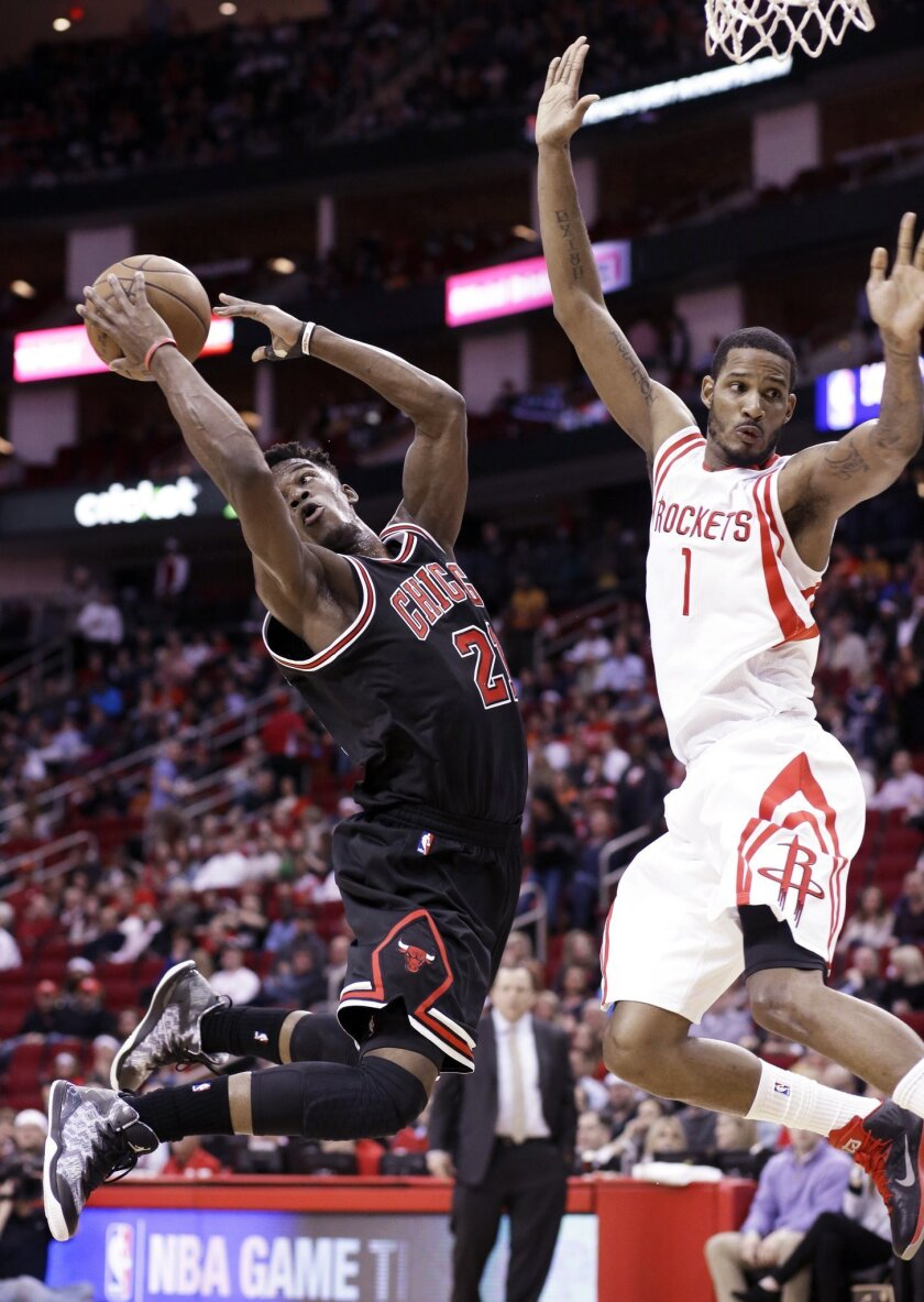 Chicago Bulls' Jimmy Butler (21) tries to maintain control of the ball as Houston Rockets' Trevor Ariza (1) defends the basket in the first half of an NBA basketball game Wednesday, Feb. 4, 2015, in Houston. (AP Photo/Pat Sullivan)