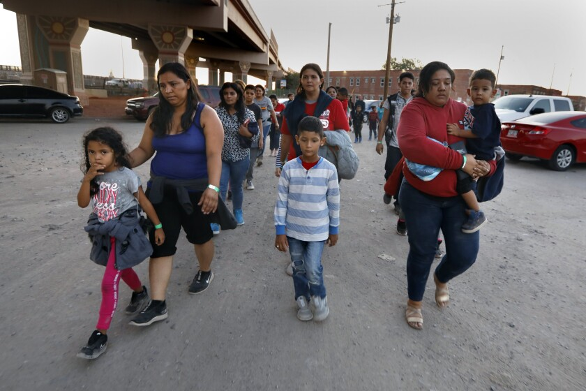 A group of about 50 migrants are led by U.S. Border Patrol agents and police officers to a holding area in El Paso after they crossed into the United States to seek political asylum.
