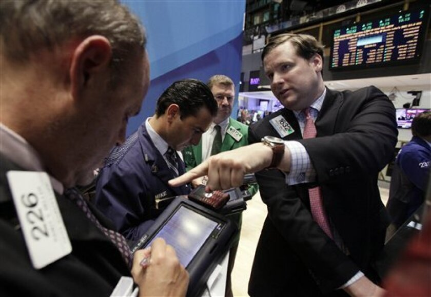 Specialist Gregg Maloney, right, works on the floor of the New York Stock Exchange Wednesday, Nov. 30, 2011. A move by the world's central banks to lower the cost of borrowing exhilarated investors Wednesday, sending the Dow Jones industrial average soaring 490 points and easing fears of a global credit crisis similar to the one that followed the 2008 collapse of Lehman Brothers. It was the Dow's biggest gain since March 2009. (AP Photo/Richard Drew)