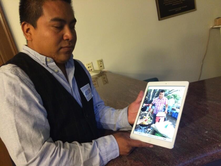 Santos Martínez sostiene la foto de su hermano.