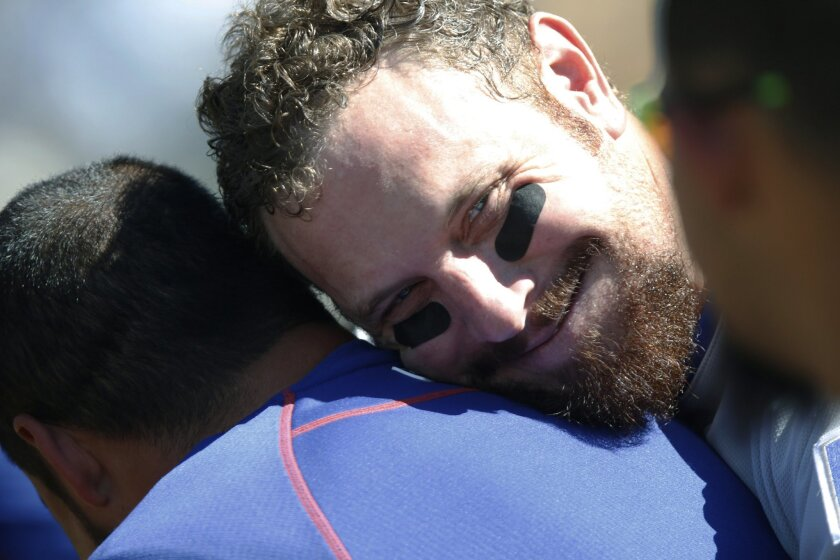 Texas Rangers left fielder Josh Hamilton, right, jokes with a member of the team's staff between the fifth and sixth innings of the Rangers' baseball game against the Colorado Rockies on Wednesday, July 22, 2015, in Denver. Texas won 10-8. (AP Photo/David Zalubowski)
