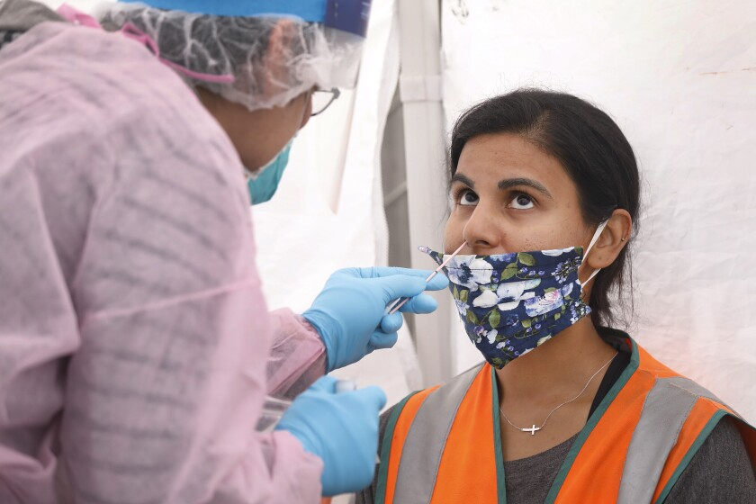 A woman gets a COVID-19 nasal swab test