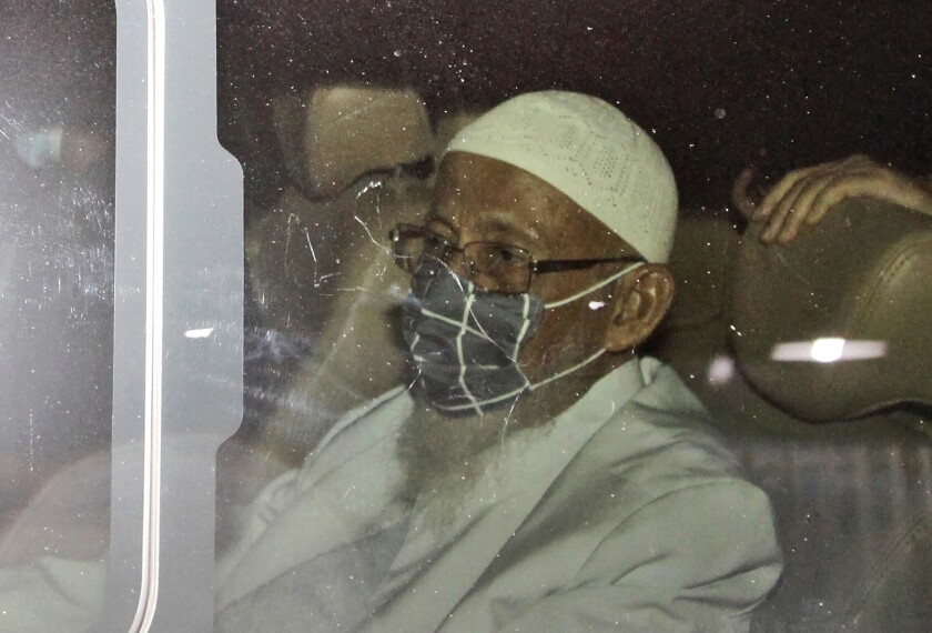 Islamic cleric Abu Bakar Bashir sits inside a van as he leaves upon his release from Gunung Sindur Prison in Bogor, West Java, Indonesia, Friday, Jan. 8, 2021. The convicted firebrand cleric who inspired the Bali bombers and other violent extremists walked free from prison Friday after completing his sentence for funding the training of Islamic militants. (AP Photo/Aditya Irawan)